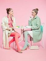 zwei Mädchen blonde Haare fünfziger Jahre Mode-Stil trinken Tee. foto