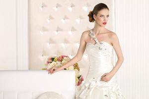 wunderschöne Braut in einem weißen Raum foto