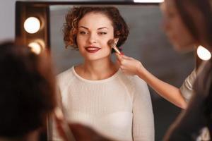 attraktives Mädchen, das vor dem Spiegel sitzt foto