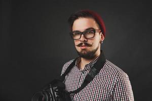 hübscher Kerl mit Bart, der Weinlesekamera hält foto