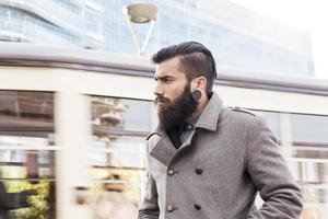 Porträt des jungen Hipster-Geschäftsmannes um eine moderne Stadt foto