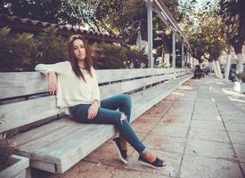 Porträt des jungen Mädchens, das auf der Bank sitzt foto