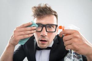Hipster putzt seine Brille foto