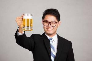 asiatischer Geschäftsmann jubelt mit einem Becher Bier