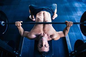 muskulöses Manntraining mit Langhantel auf Bank foto