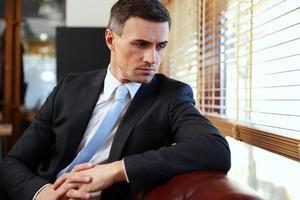 Geschäftsmann sitzt und schaut in Fenster foto