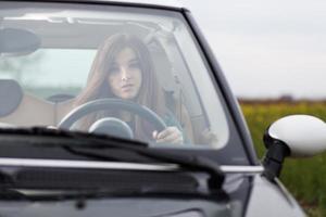 junge schöne Frau, die ein Auto fährt foto