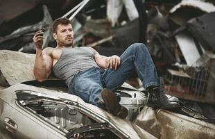 Der Mann ruht sich auf einem Autowrack aus foto