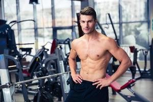 schöner Fitness-Mann, der im Fitnessstudio steht foto