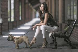 Brünette Frau sitzt mit Hund foto