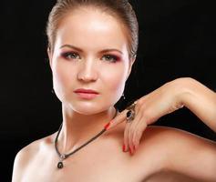 Porträt der hübschen jungen Frau mit Perlen und Ringen an foto