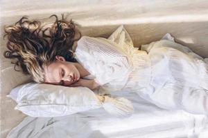 schöne Frau mit langen Haaren, die im Sonnenlicht schlafen foto
