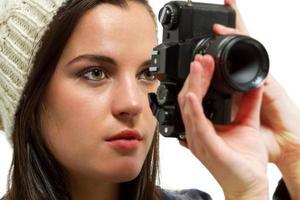 süßes Mädchen in Strickmütze beim Fotografieren