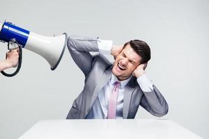 Geschäftsmann, der seine Ohren vom Megaphon bedeckt foto