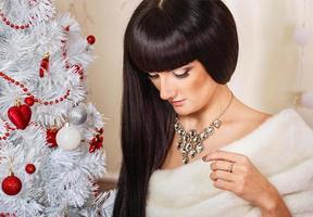 Porträt des Mädchens nahe dem Weihnachtsbaum