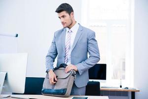 hübscher Geschäftsmann, der Tasche auf dem Tisch schließt foto