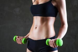 Körper der jungen fit Frau, die Hanteln hebt