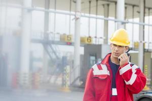 männlicher Arbeiter mit Walkie-Talkie im Versandhof foto