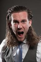 ausdrucksstarkes Gesicht des jungen Mannes mit langem Haar, das Anzug und Krawatte trägt. foto
