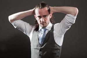 ausdrucksstarkes Gesicht des jungen Mannes mit langem Haar, das Anzug und Krawatte trägt.