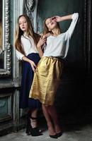zwei schöne Frauen, die im veralteten Innenraum aufwerfen. foto