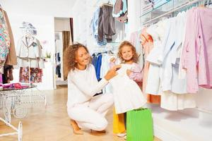 kleines lächelndes Mädchen mit schöner Mutter einkaufen foto