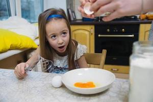 kleines Mädchen wird den Teig für Pfannkuchen schlagen foto