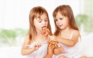 glückliche Mädchen Zwillingsschwestern mit Lutscher Süßigkeiten