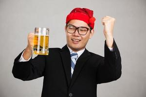 glücklicher asiatischer Geschäftsmann mit Partyhut betrinkt sich mit Bier
