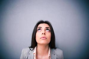 Nahaufnahmeporträt der attraktiven jungen Frau, die oben schaut foto