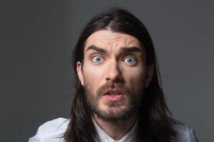 wütender Mann mit Bart und langen Haaren, die Kamera betrachten foto