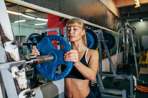 sportliches Mädchen legt Gewicht auf Langhantel im Fitnessstudio foto