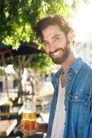 Mann, der mit erfrischendem Bier an der Bar im Freien im Sommer lächelt foto
