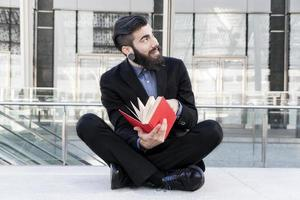 junger Hipster, der ein Buch liest, das draußen sitzt