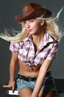 schönes Rodeomädchen, das einen Cowboyhut trägt foto