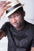 afrikanischer Mann mit Hut, der auf Couch sitzt foto