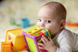Junge beißt Spielzeug foto