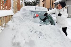 Frau, die Schnee vom Auto reinigt foto