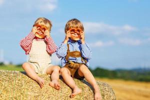 zwei kleine Geschwisterjungen und Freunde, die auf Heuhaufen sitzen foto