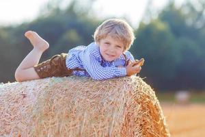lustiger kleiner Junge, der auf Heuhaufen liegt und lächelt foto