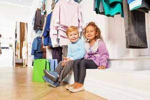 Junge und Mädchen sitzen unter Kleiderbügeln mit Kleidern foto