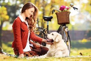 schöne Frau, die mit ihrem Hund auf einem Gras sitzt foto