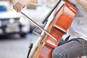 Typ, der im Sommer auf der Straße Cello spielt foto