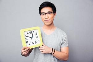 glücklicher asiatischer Mann, der große Uhr hält foto