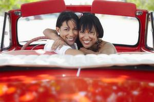 schöne Zwillingsschwestern, die im Cabrioletauto umarmen