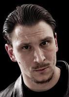 hübsches Mann-Nahaufnahmeporträt auf schwarzem Hintergrund