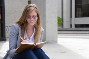 glückliche Frau, die in ihr Tagebuch schreibt foto