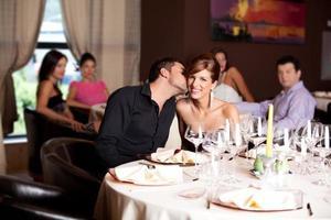 glückliches Paar am Restauranttisch küssen foto