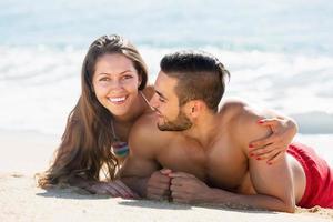 glückliche Liebhaber, die auf Sandstrand ruhen foto