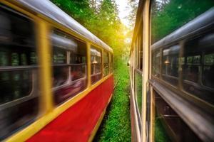schnelle Straßenbahn fährt gedankengrüner sonniger Wald